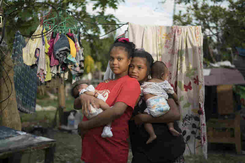 Sisters Rose Ann, age 15, (right) and Ros Jane, age 17, hold their babies in the neighborhood where they live in Manila.