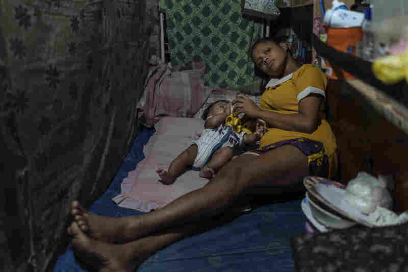 Ros Jane and her son in the room she shares with her sister and her child. While their situation is bleak, the sisters support each other, creating an ad-hoc safety net to face the challenges of teen motherhood.
