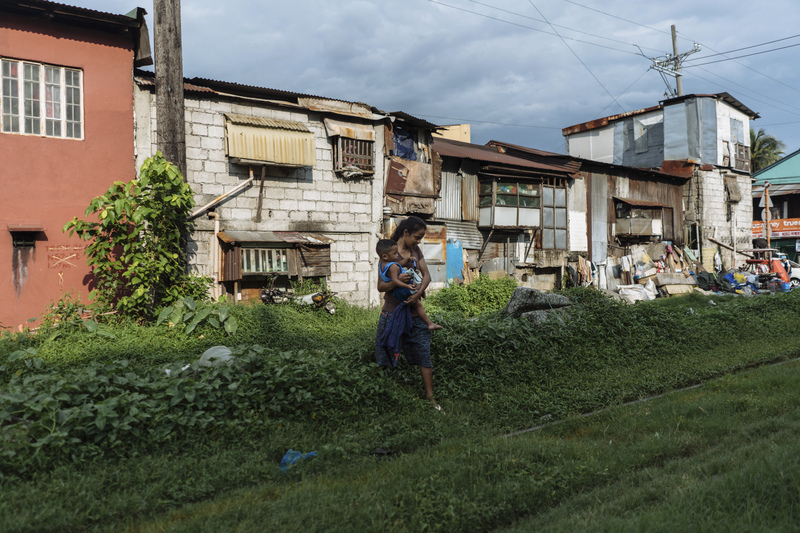 Ros Jane walks with her child by the railway near her home in Manila. She became pregnant at age 16.
