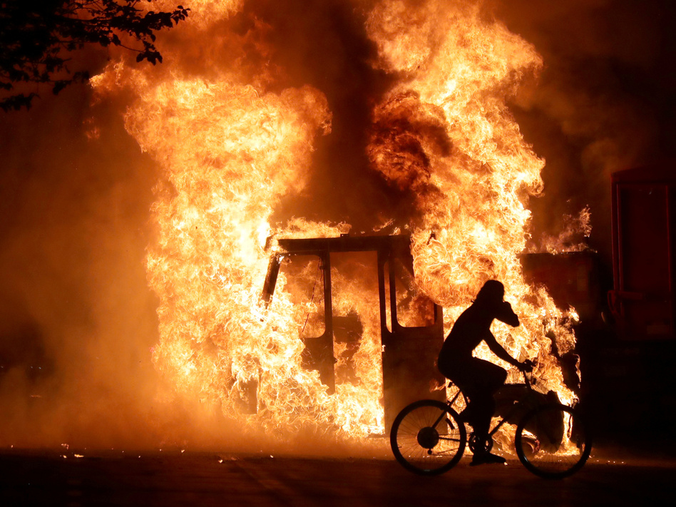 A man on a bike rides past a city truck on fire outside the Kenosha County Courthouse in Kenosha, Wis., during protests following the police shooting of Jacob Blake, a Black man, on Sunday. (Mike De Sisti/Milwaukee Journal Sentinel via USA Today/Via Reuters)