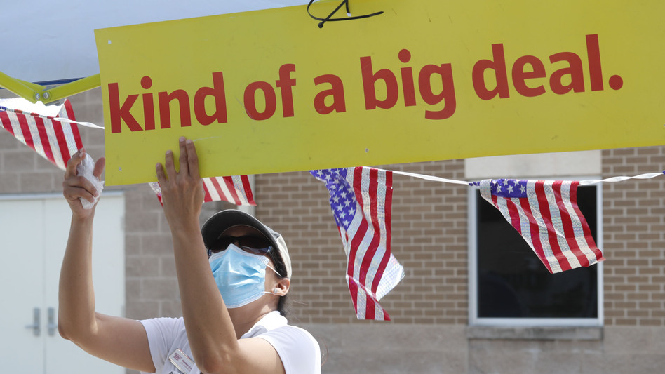 U.S. Census Bureau worker Marisela Gonzales adjusts a sign at a walk-up counting site for the 2020 census in Greenville, Texas, in July. (LM Otero/AP)