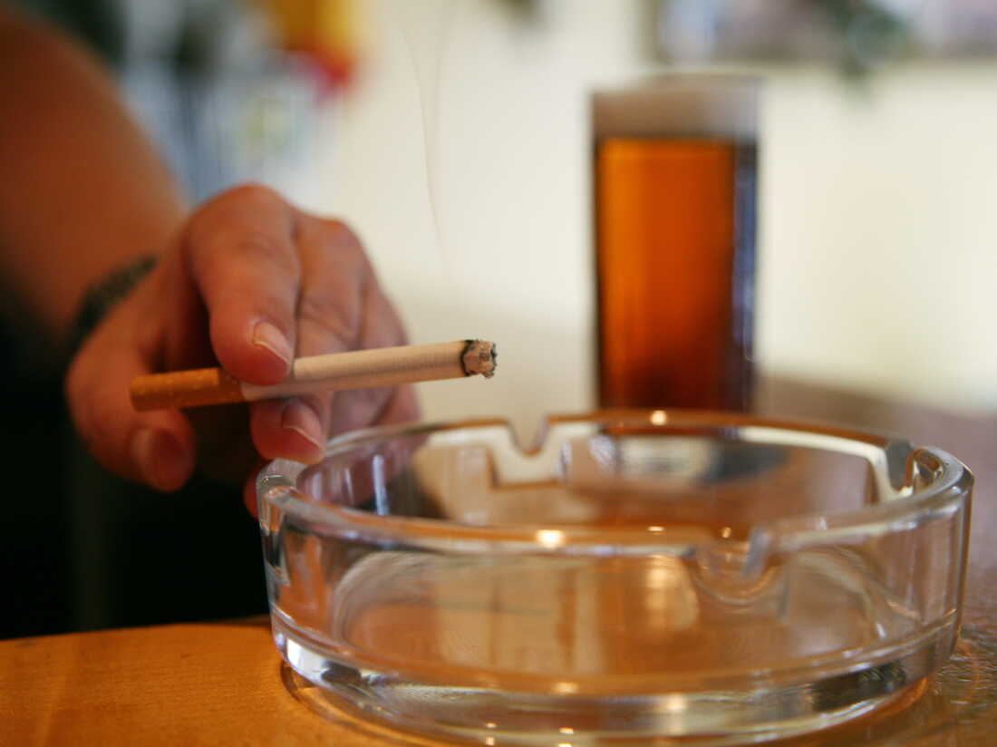 A man holds a cigarette over an ashtray in a pub in Essen, western Germany, on July 6, 2010. AFP PHOTO PATRIK STOLLARZ (Photo credit should read PATRIK STOLLARZ/AFP via Getty Images)