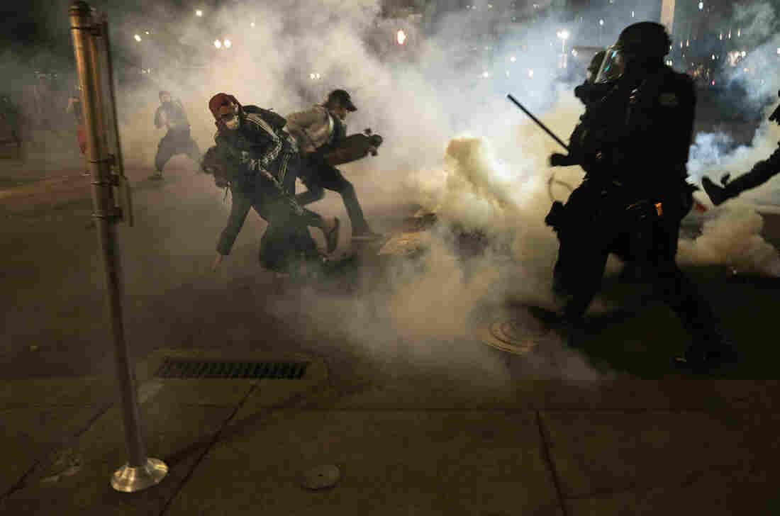 Protests erupt at Portland police building, mayor's condo
