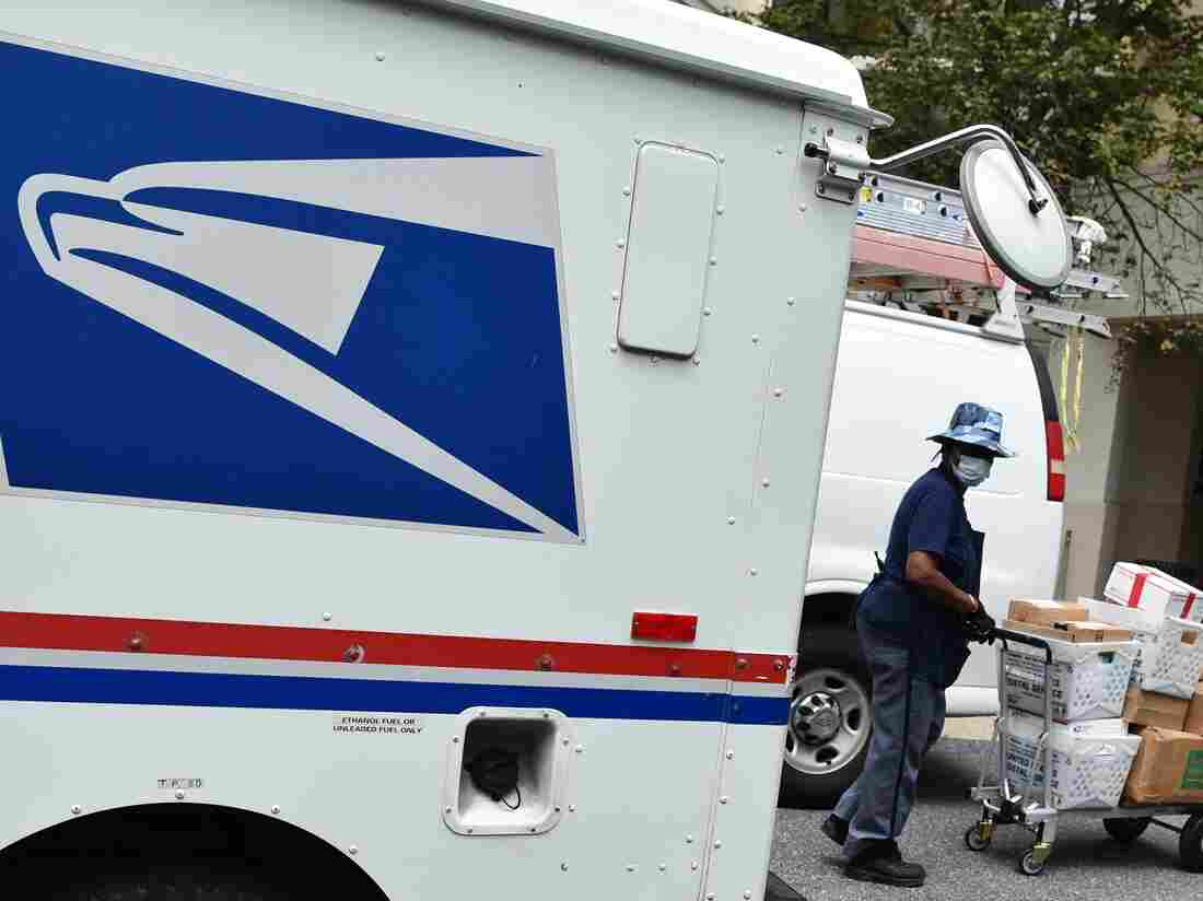 A mail carrier delivers mail to an apartment building in Bethesda, Maryland on August 21, 2020. (Photo by MANDEL NGAN / AFP) (Photo by MANDEL NGAN/AFP via Getty Images)