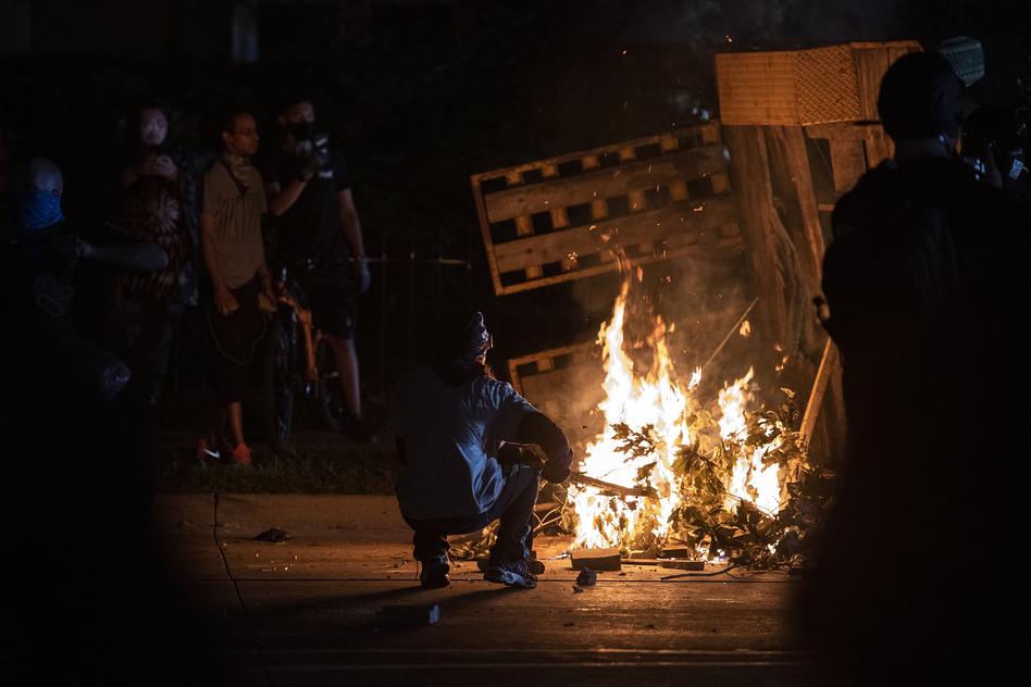 A protester in Kenosha lights some debris on fire on Aug. 26, 2020. (Angela Major/Angela Major/WPR)