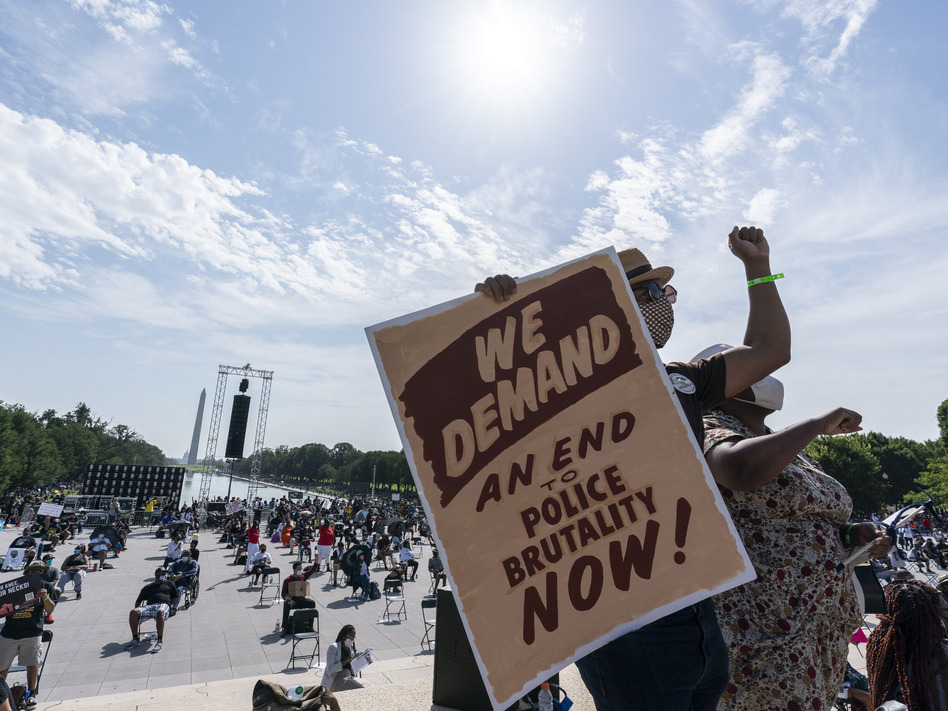 """People attend the Commitment March on Friday at the Lincoln Memorial in Washington, D.C., on the 57th anniversary of the March on Washington and the Rev. Martin Luther King Jr.'s """"I Have a Dream"""" speech. (Alex Brandon/AP)"""