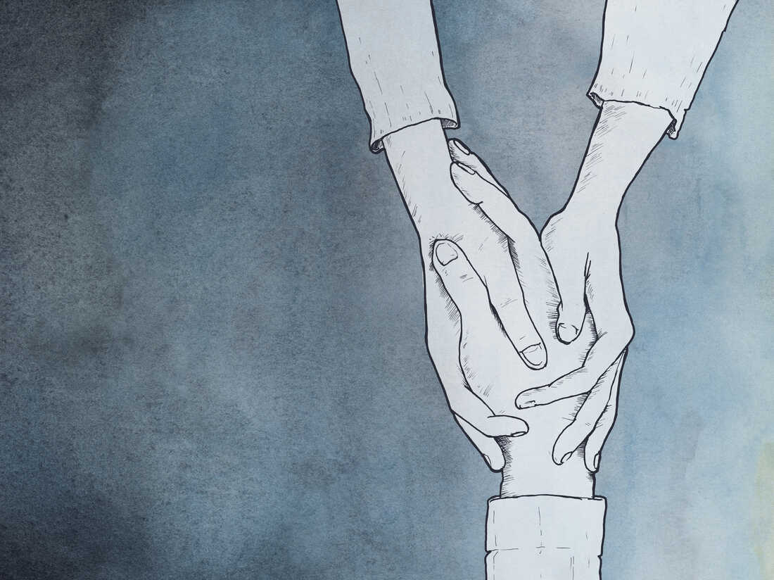 One hand clasping another hand in a gesture of empathy.
