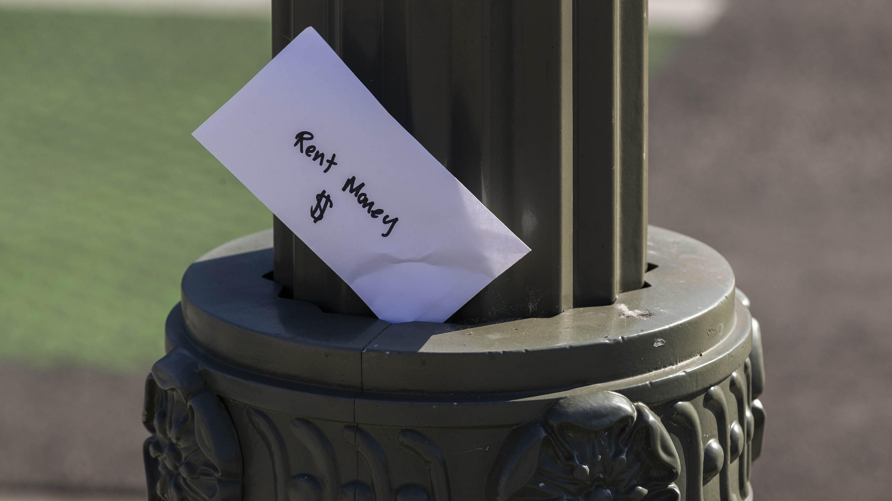 """A paper envelope written with the words """"Rent Money $"""" is left tucked in a lighting pole in April in the Boyle Heights area of Los Angeles. Amid massive job losses due to COVID-19, California Gov. Gavin Newsom signed an extended eviction moratorium on Monday."""
