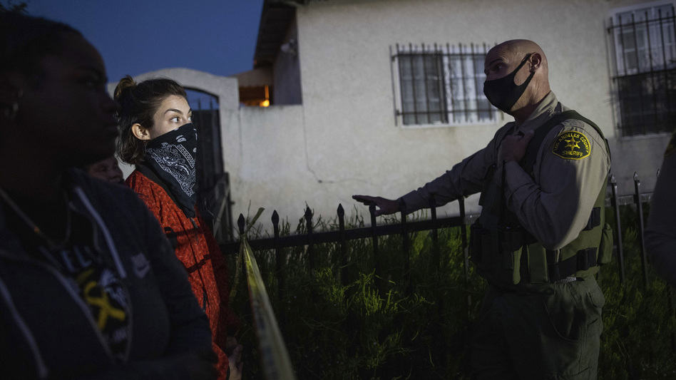 A protester talks with a deputy of the Los Angeles Sheriff's Department during demonstrations following the death of a Black man identified as Dijon Kizzee on Monday in Los Angeles. (Christian Monterrosa/AP)