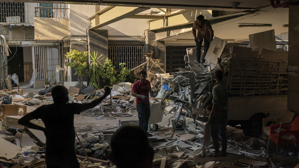 Workers remove debris from a hospital that was heavily damaged in last month
