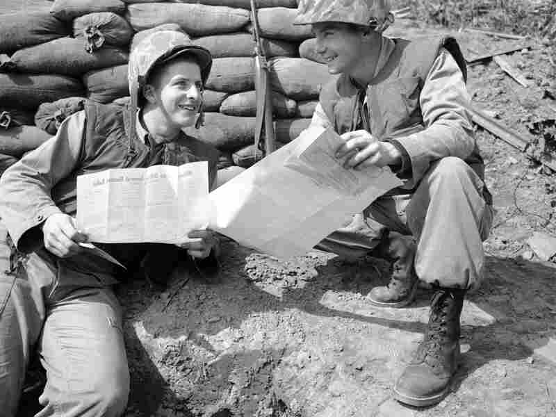 Two marines talk over their absentee ballots outside a bunker at battalion headquarters in Korea, Nov. 4, 1952.