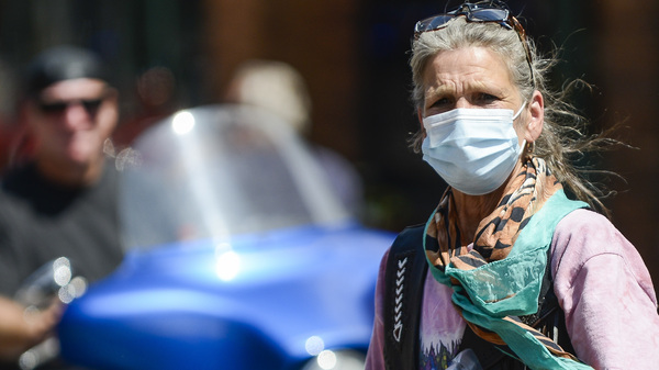 A woman crosses the street as motorcyclists ride through Deadwood, S.D., during the Sturgis Motorcycle Rally. Despite the pandemic, this year