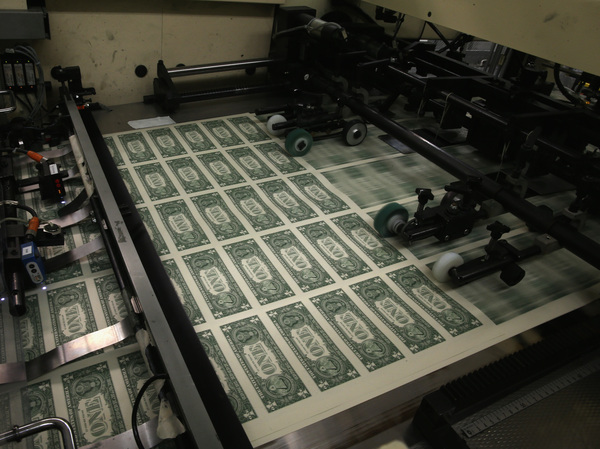 Sheets of one-dollar bills run through the printing press at the Bureau of Engraving and Printing on March 2015 in Washington, D.C. National debt is expected to reach an all-time high of 107% of GDP in 2023.