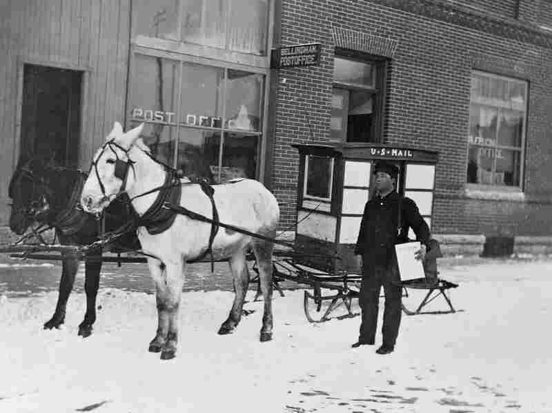 A mailman uses a horse-drawn sled to deliver the mail over snow.