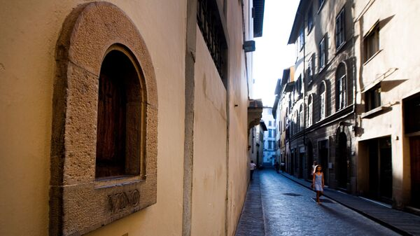 A girl walks past a buchetta del vino, a small window to serve wine, typical in Florence.