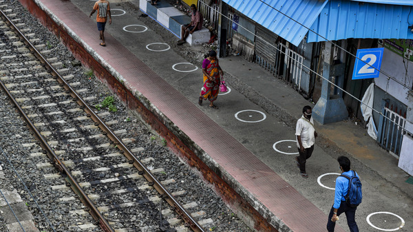 People walk through a railway station platform marked with circles to maintain physical distance in Kolkata, India, Monday. India