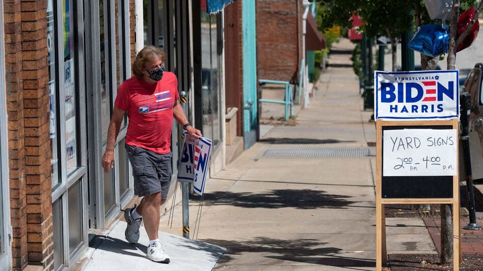 A man walks out of the Washington County Democratic Party office last week, in the suburbs of Pittsburgh, after taking a Joe Biden yard sign. Because of the coronavirus pandemic, Biden's campaign isn't doing any in-person door-knocking. (Andrew Caballero-Reynolds/AFP via Getty Images)