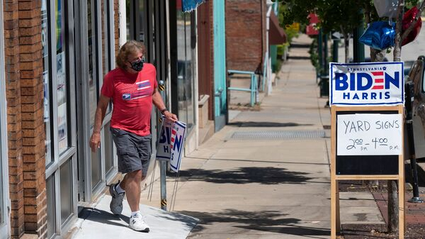 A man walks out of the Washington County Democratic Party office last week, in the suburbs of Pittsburgh, after taking a Joe Biden yard sign. Because of the coronavirus pandemic, Biden