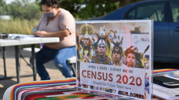 A sign promoting participation in the 2020 census is displayed as Selena Rides Horse enters information into a phone for a member of the Crow Indian Tribe in Lodge Grass, Mont. in August.