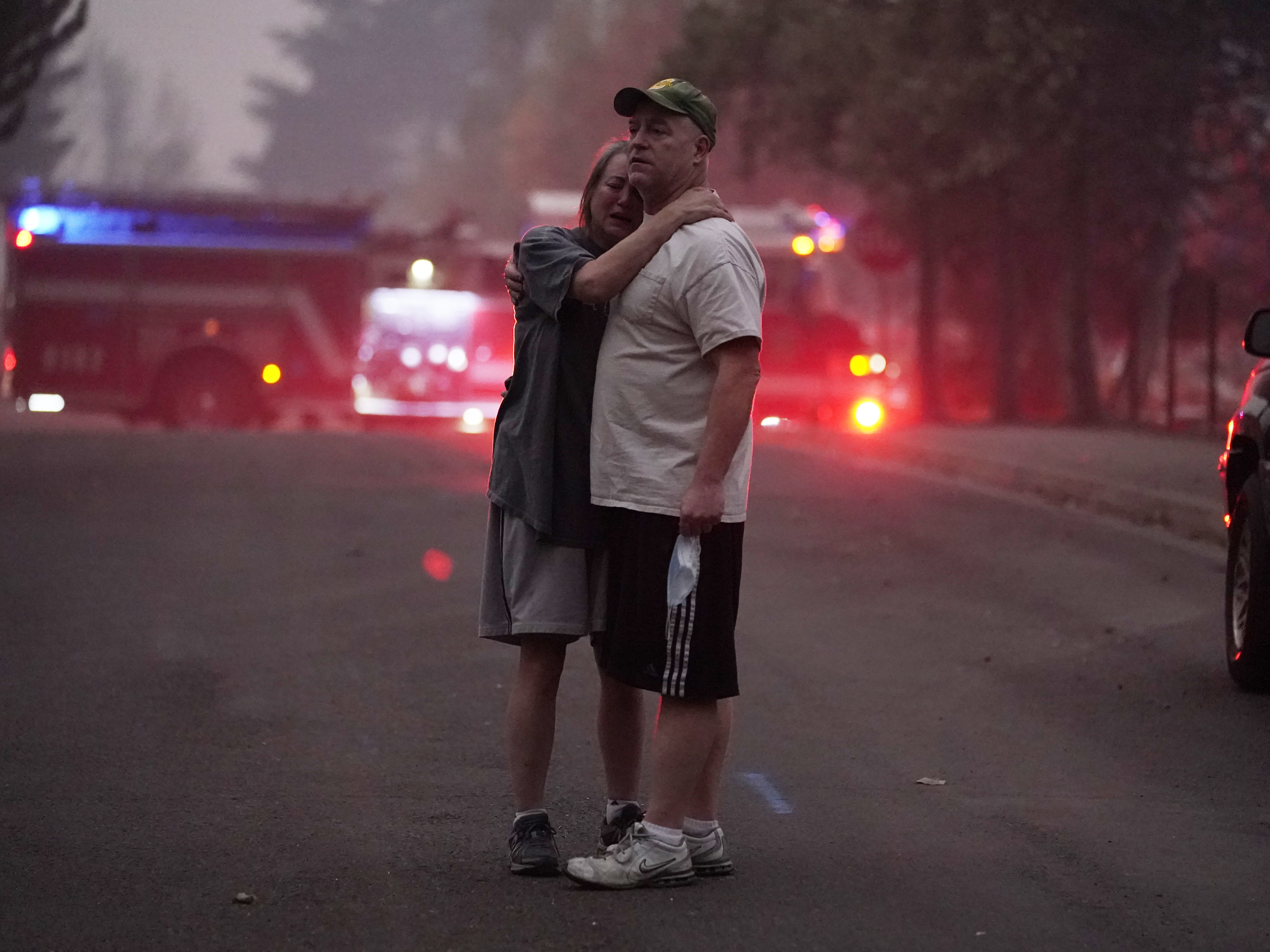 A couple embrace Thursday while touring an area devastated by the Almeda Fire in Phoenix Ore