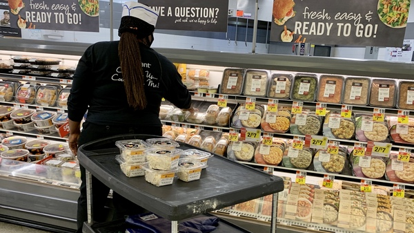 Grocery prices have fallen in recent months but are still 4.6% higher than at this time last year. Here, a woman stock shelves in a deli in June at a Washington, D.C., supermarket.