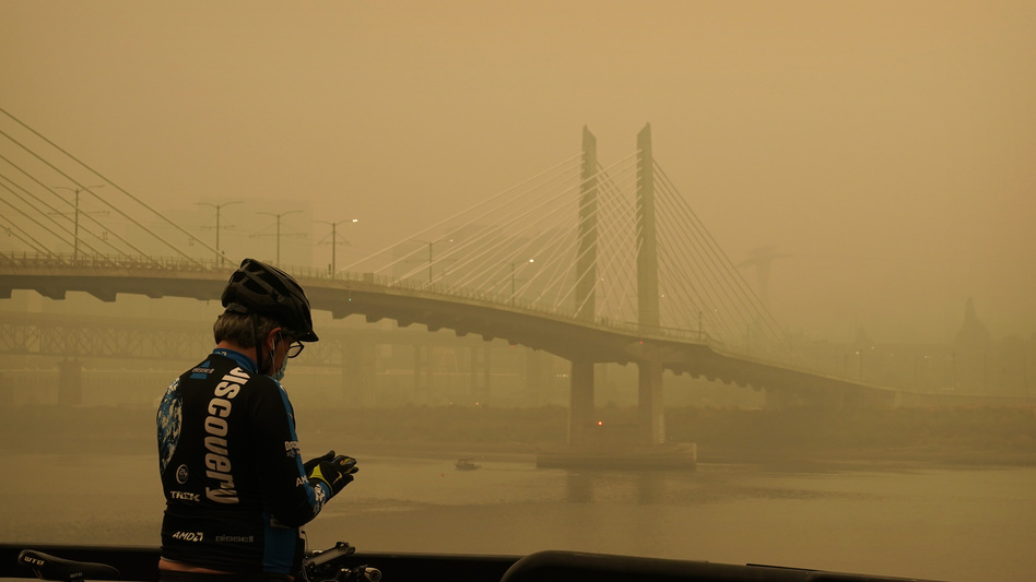 A man stops on his bike Saturday along the Willamette River as smoke from wildfires partially obscures the Tilikum Crossing Bridge in Portland, Ore. (John Locher/AP)