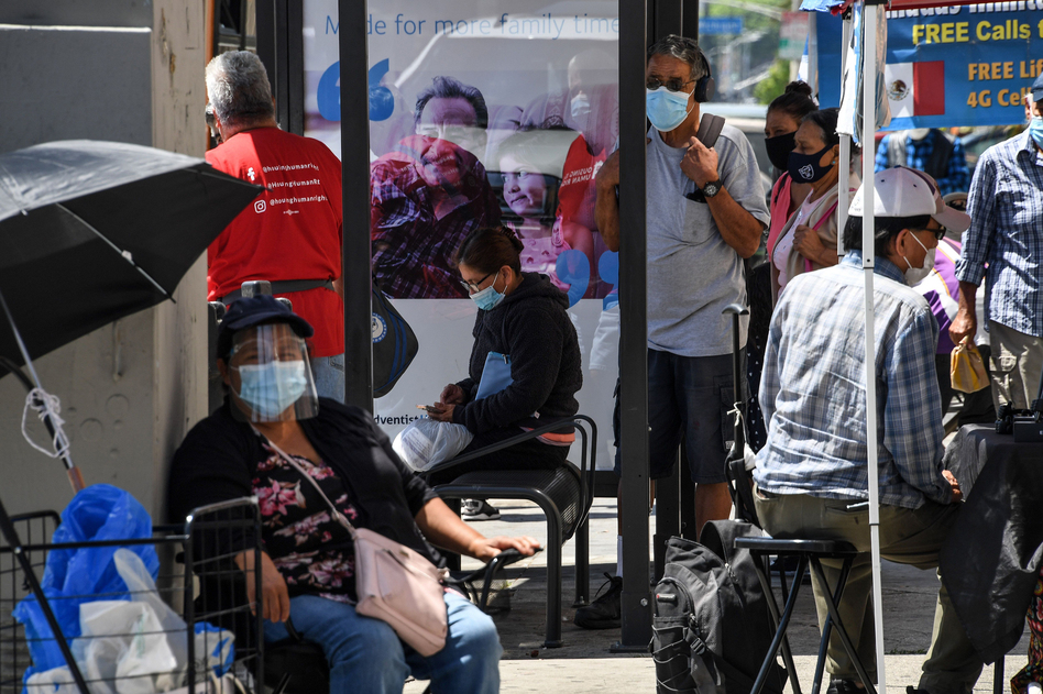 People wait for a bus in August in East Los Angeles. Latinos have the highest rate of labor force participation of any group in California — many in public-facing jobs deemed essential. That work has put them at higher risk of catching the coronavirus. (Robyn Beck/AFP via Getty Images)
