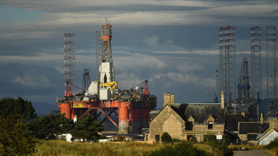 An oil rig towers over houses last week in Nigg, Scotland. Major players in the oil industry expect depressed oil demand and low prices to continue well into next year. (Peter Summers/Getty Images)