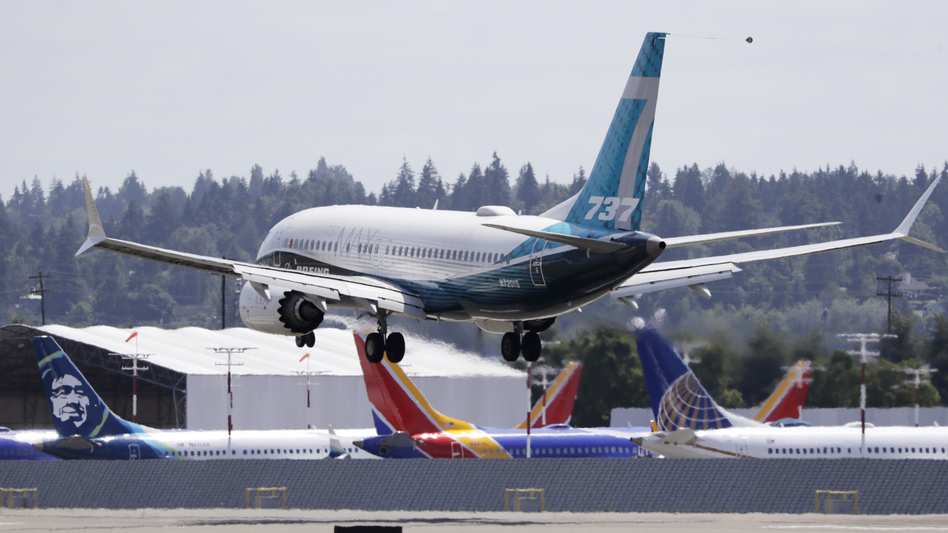 A Boeing 737 Max heads to a landing past grounded Max jets at Seattle's Boeing Field after a test flight in June. It was the first of three days of recertification test flights that mark a step toward returning the aircraft to passenger service. (Elaine Thompson/AP)