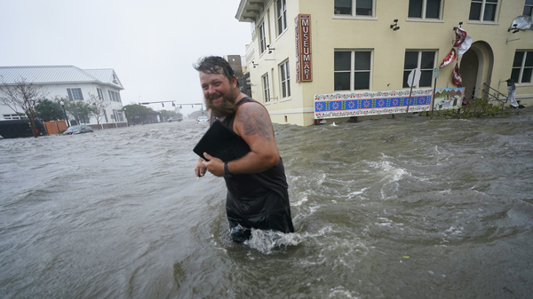 Trent Airhart wades through flood waters after retrieving items from his vehicle in downtown Pensacola, Fla., Wednesday. Hurricane Sally is causing flooding across a wide area of the northern Gulf Coast.