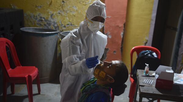 A health worker wearing protective gear collects a swab sample during a medical screening for the coronavirus in Mumbai on Wednesday. The number of registered coronavirus cases passed 5 million on Wednesday.