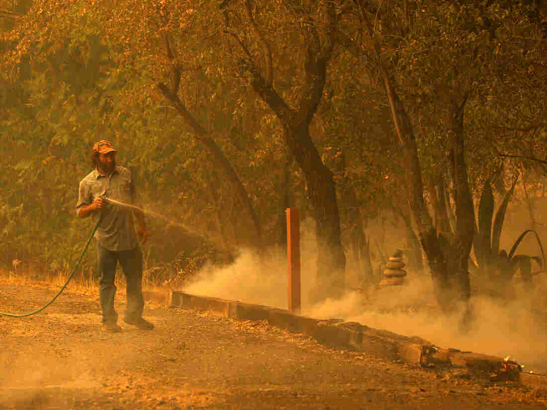 FAIRFIELD, CALIFORNIA - AUGUST 19: A resident uses a garden hose as he extinguishes spot fires while protecting his property as the LNU Lightning Complex fire burns through the area on August 19, 2020 in Fairfield, California.  (Photo by Justin Sullivan/Getty Images)