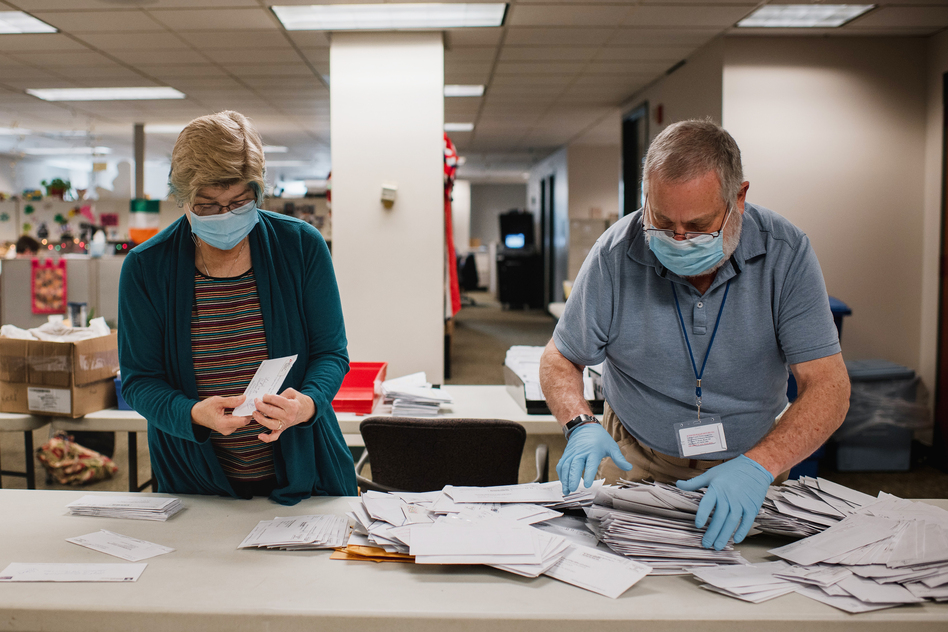 Andrea Lerner (left), and her husband, Ira Lerner, sift through the mail-in applications at the Voter Registration office in the Lehigh County Government Center in Allentown, Pa. (Hannah Yoon for NPR)