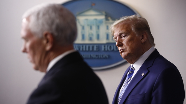 President Trump listens as Vice President Mike Pence speaks during a coronavirus task force briefing at the White House in April.
