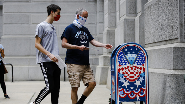 Benjamin Graff, center, and his son Jacob Graff, 19, drop off their mail-in ballots for the Pennsylvania primary election, in Philadelphia, on June 2, 2020. The state Supreme Court affirmed Thursday that counties may use drop boxes for voters casting mail-in ballots.