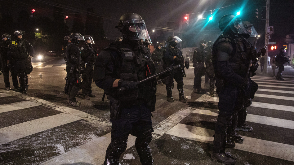 Police stand guard as protesters take to the streets on Sept. 4 in Portland, Ore. (Paula Bronstein/AP)