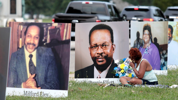 Images of Detroit-area residents who died from COVID-19 line a street during a drive-through memorial on Sept. 1 on Belle Isle in Detroit. The number of U.S. dead has crossed the 200,000 mark — and the figure could nearly double by the end of the year, experts say.