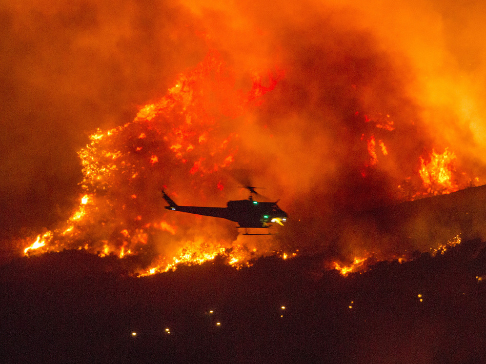 A helicopter prepares to drop water at a wildfire in Yucaipa, Calif., on Sept. 5. A firefighter was killed in the El Dorado blaze on Thursday. (Ringo H.W. Chiu/AP)