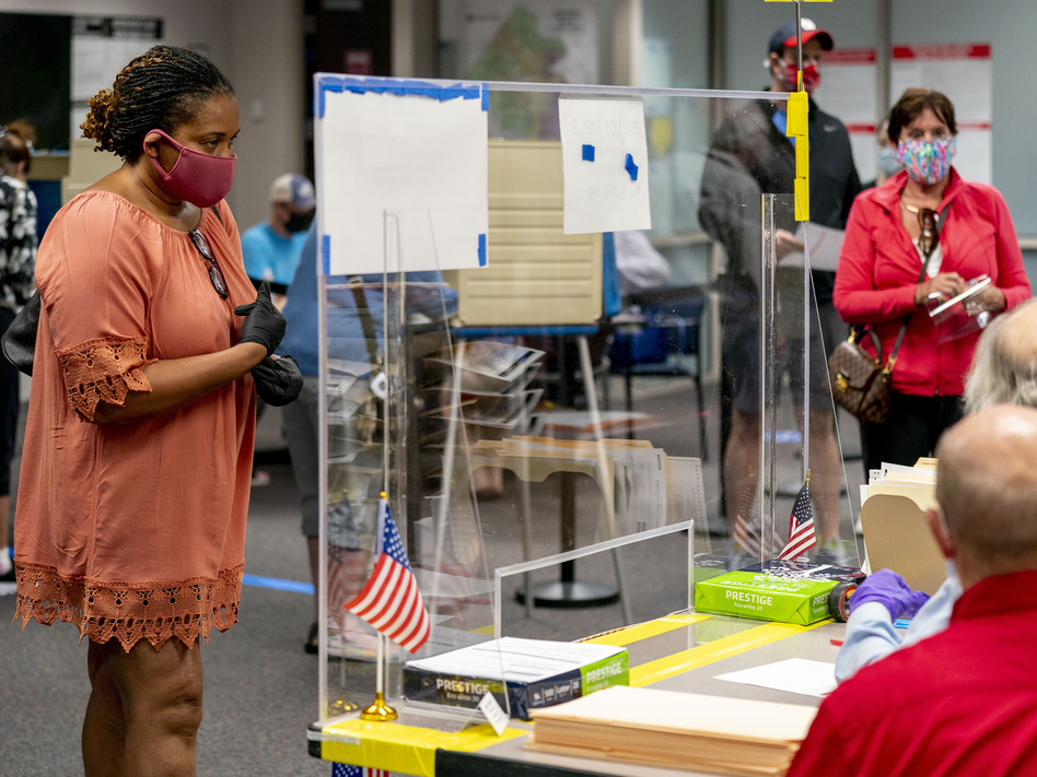 A voter stands by for her ballot as people wait more than four hours for early voting Friday in Fairfax, Va. (Andrew Harnik/AP)