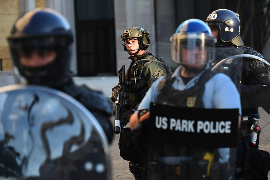 U.S. Park Police and other federal officers hold a perimeter near the White House on June 1 as demonstrators gather to protest the killing of George Floyd.