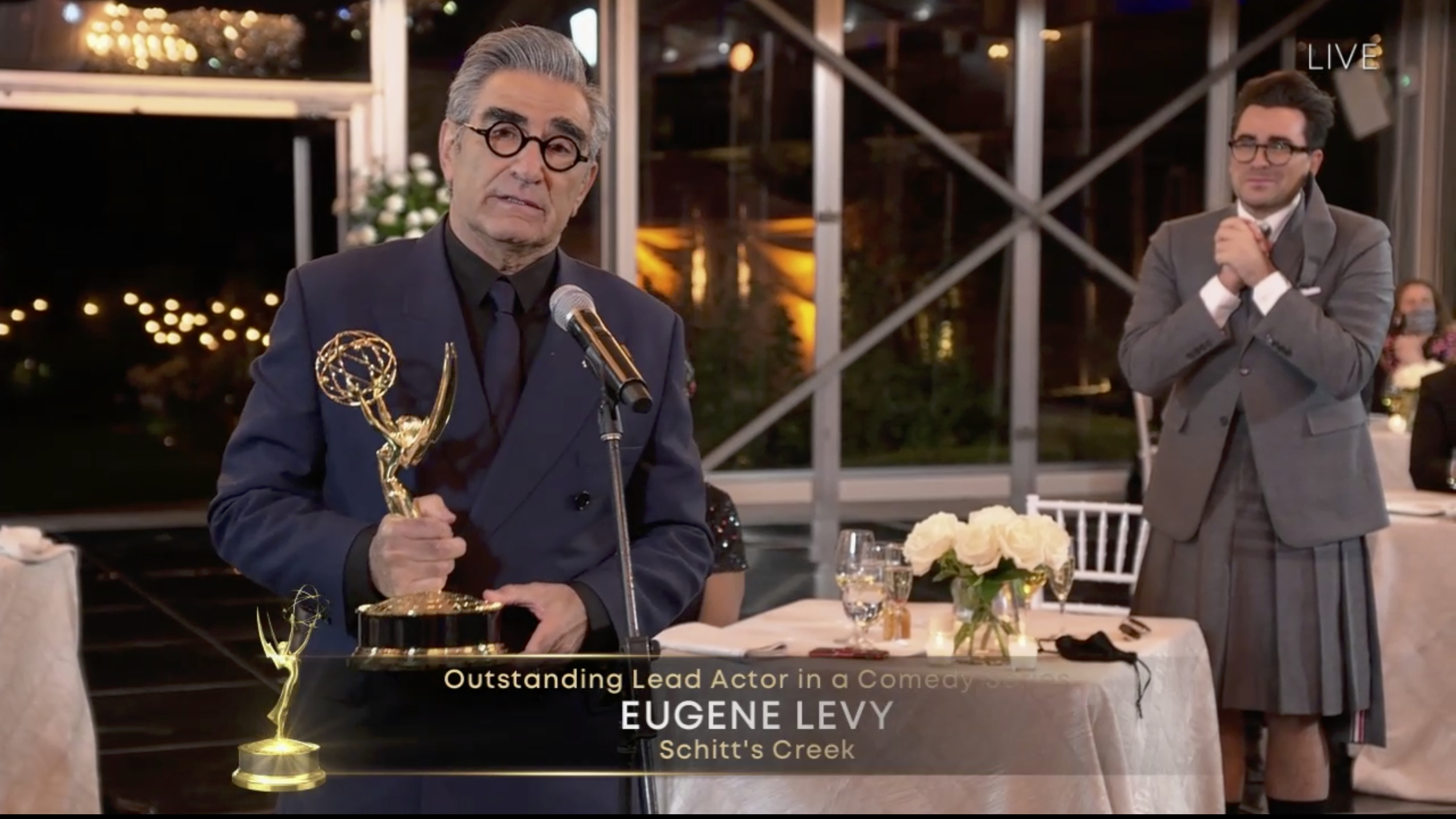 Eugene Levy accepts his award for lead actor in a comedy series for Schitt's Creek as his son (and creative partner) Dan Levy looks on at Sunday night's Emmy Awards.
