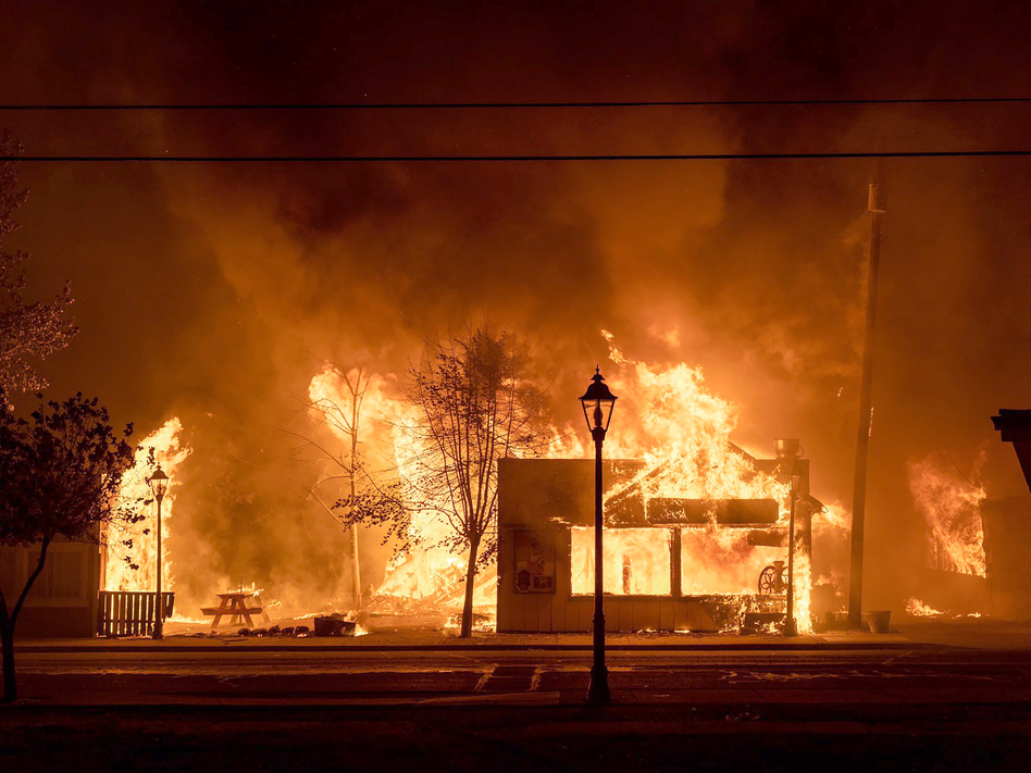 Buildings are engulfed in flames as a wildfire ravages Talent, Ore., on Sept. 8, 2020. Unfounded rumors that left-wing activists were behind the fires went viral on social media, thanks to amplification by conspiracy theorists and the platforms' own design. (Kevin Jantzer/AP)