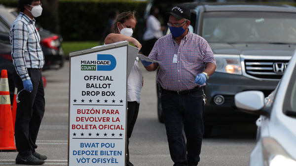Poll workers at the Miami-Dade County Elections Department deposit returned mail-in ballots into an official ballot drop box on primary election day on Aug. 18 in Doral, Fla.