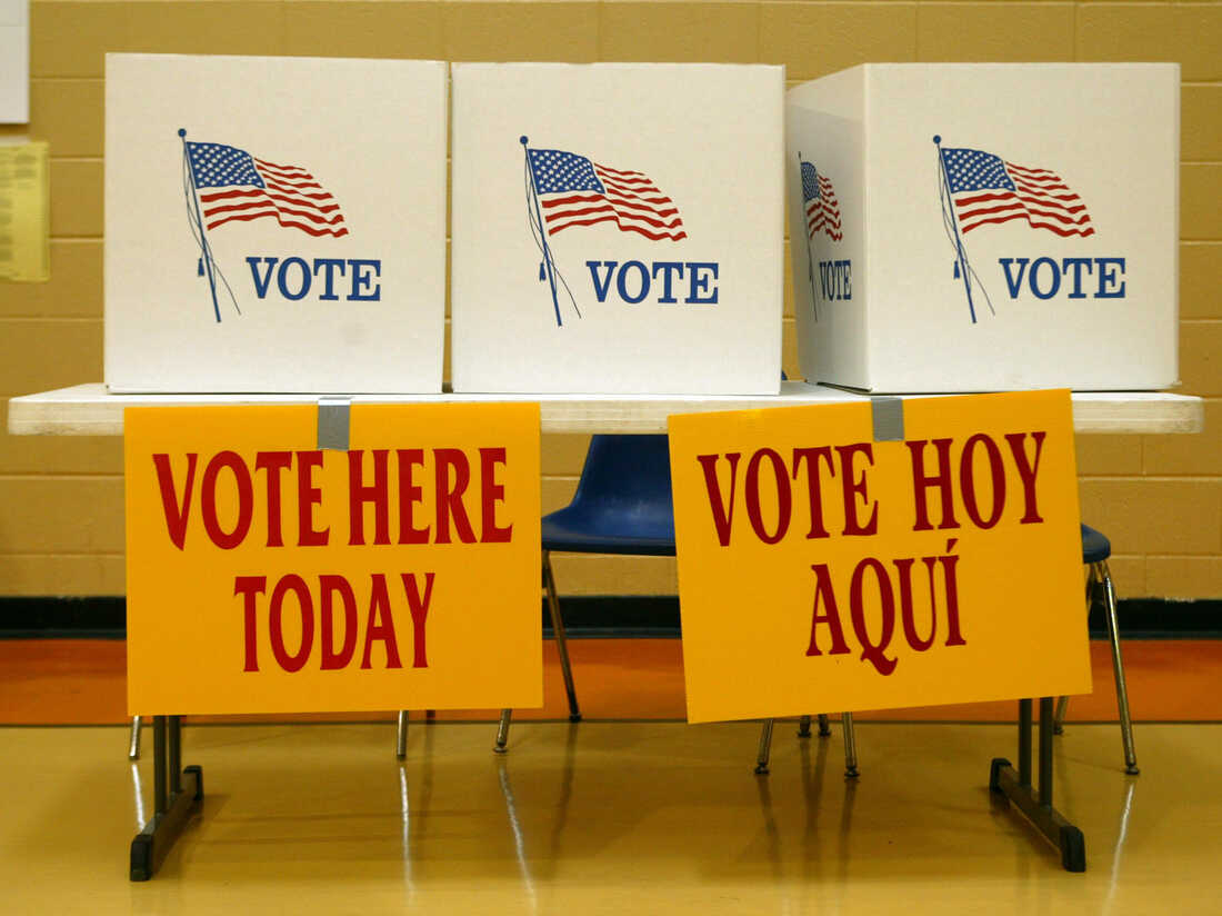Signs in English and Spanish encourage voters to cast their paper ballots. Above the signs are three cardboard polling stations. (Photo by Steven Clevenger/Corbis via Getty Images)