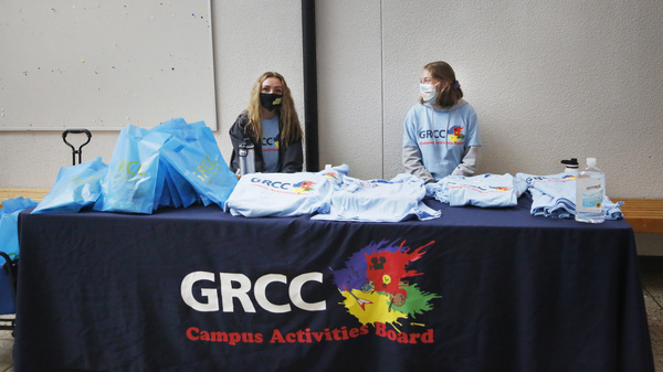 Students at Grand Rapids Community College pass out T-shirts to promote virtual student life offerings during the fall semester.