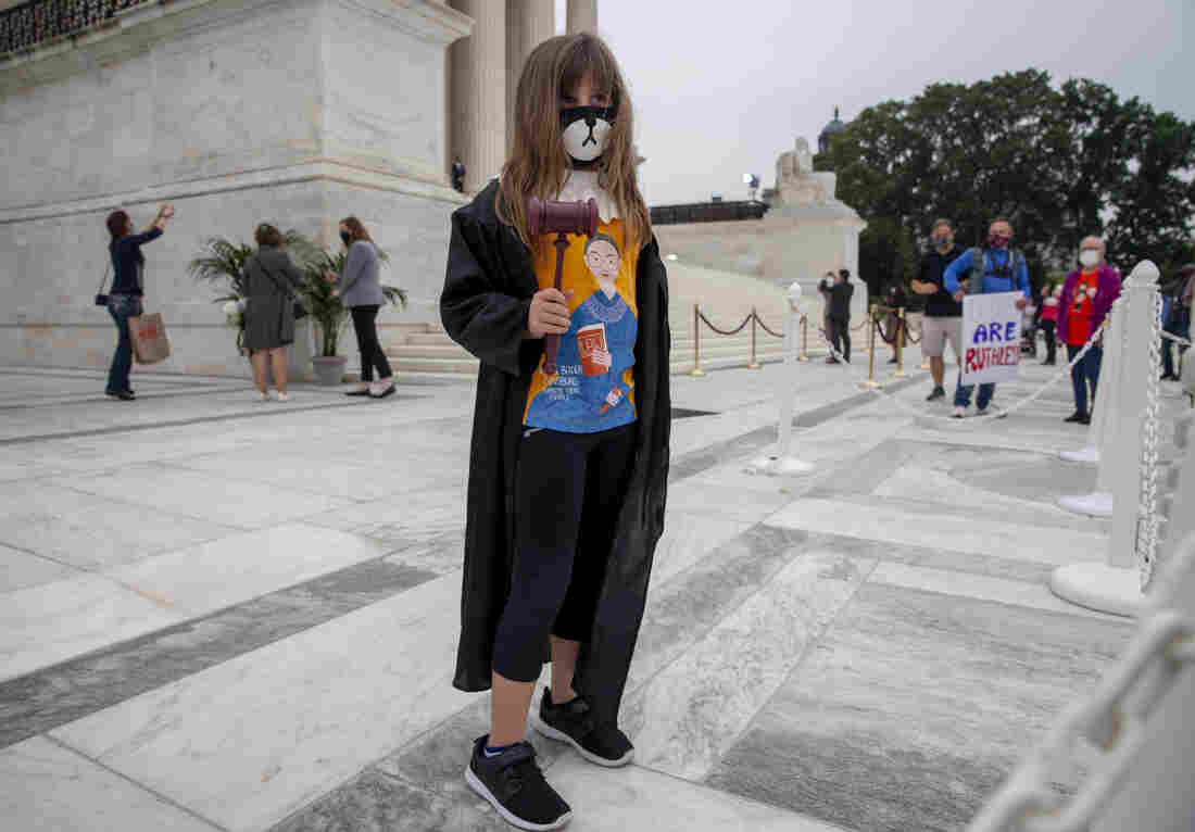 Sally Sells with her daughter, Bromwyn Sells, 7, who was wearing both a dog mask and a Justice Ginsburg judicial robe. They drove from Sarasota, Fla in order to see Justice Ginsburg lying in repose.