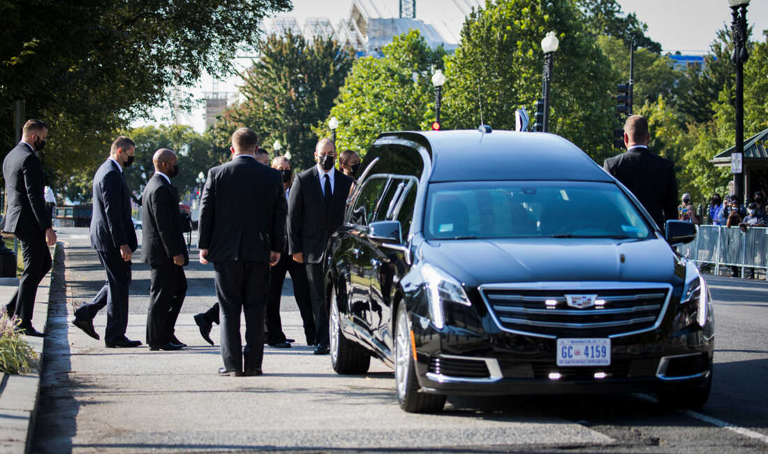 Law Clerks line up to honor the late Associate Justice Ruth Bader Ginsburg, whose flag-draped casket arrived to the U.S. Supreme Court.