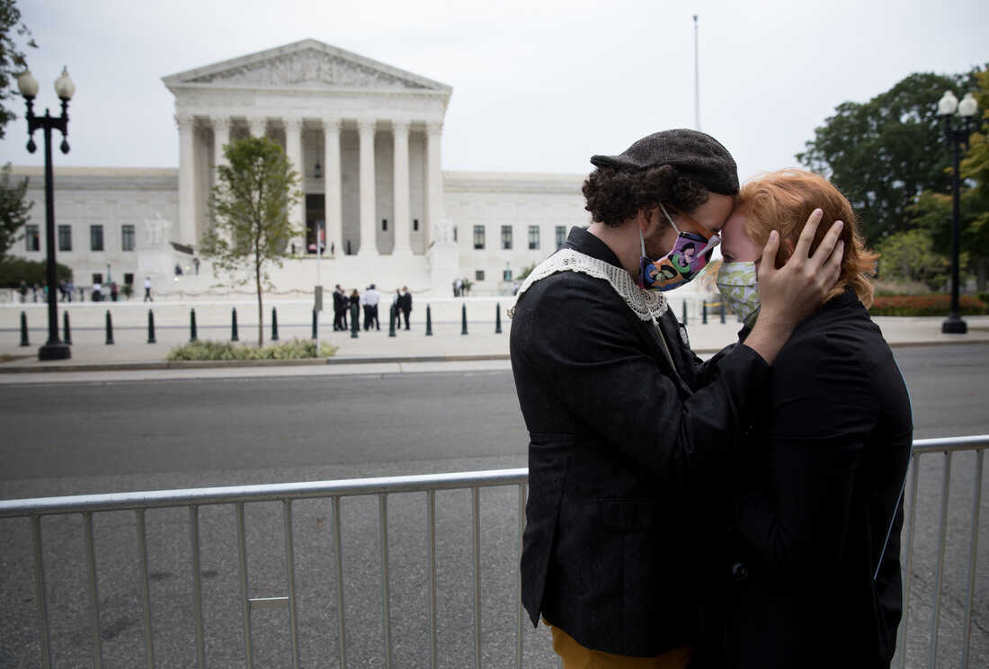 Ryan Cooper tries to calm Emily Stoinski after she was upset by a man proselytizing while they paid their respects for the late Associate Justice Ruth Bader Ginsburg.