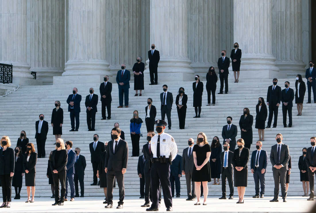 Former law clerks for Justice Ruth Bader Ginsburg stand on the steps of the U.S. Supreme Court in Washington, D.C., as they await the arrival of the casket on Wednesday.