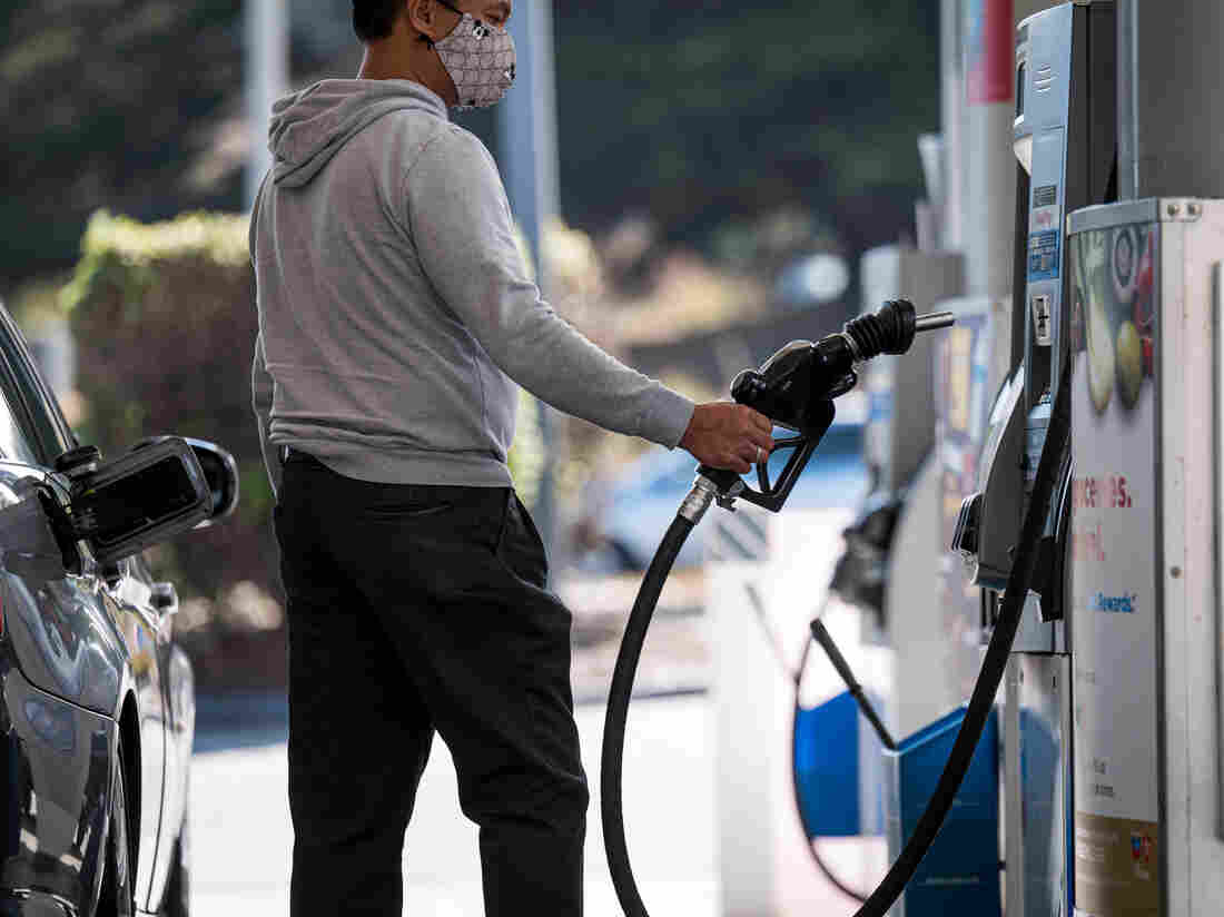 A person wearing a protective mask holds a fuel pump nozzle while refueling at a Chevron.